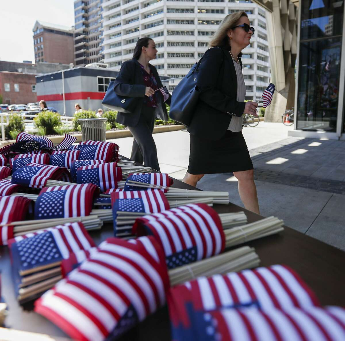 Arriving visitors walk past stacks of American flags that were being distributed before a celebration of Flag Day, Friday, June 14, 2019, in Pittsburgh. (AP Photo/Keith Srakocic)