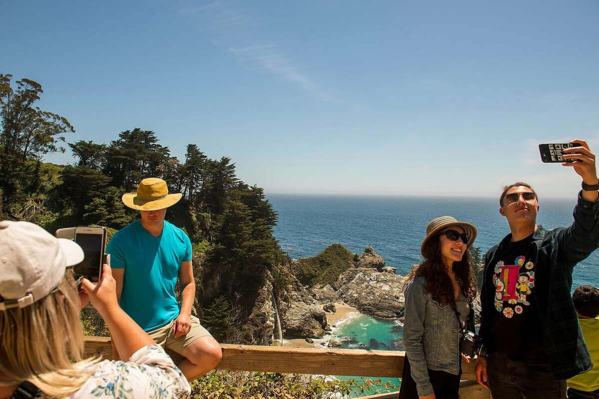 A couple takes a selfie in front of McWay Falls in Big Sur, Calif. in June 2019.