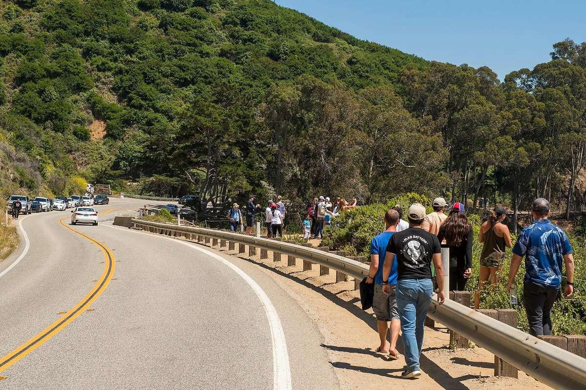 People walk along Highway 1 near McWay Falls in Big Sur, Calif. in June 2019.