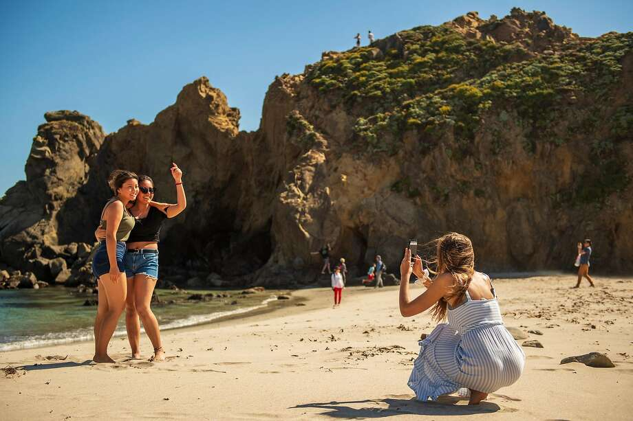 Friends take photos on Pfeiffer Beach in Big Sur, where locals complain that visitors sometimes block the road or go off-trail in search of the perfect Instagram shot. Photo: Nic Coury / Special To The Chronicle