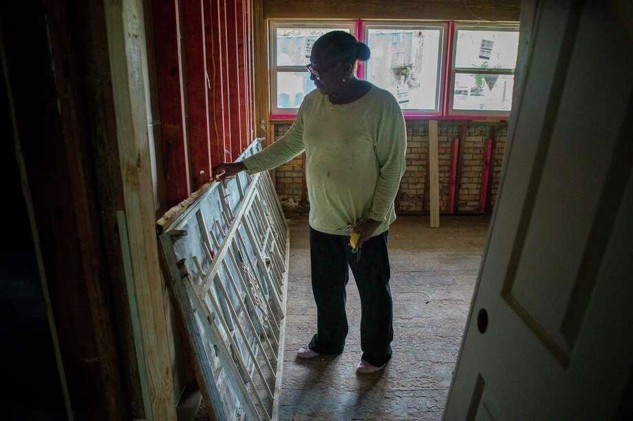 Alberta Fleming looks at her old windows and burglary bars that were taken off of her windows when they were replaced inside her northeast Houston home, Tuesday, May 28, 2019. Fleming's home was flooded during Hurricane Harvey, and now, almost two years later, it is only now starting to be repaired. Photo: Mark Mulligan,  Houston Chronicle / Staff Photographer / © 2019 Mark Mulligan / Houston Chronicle