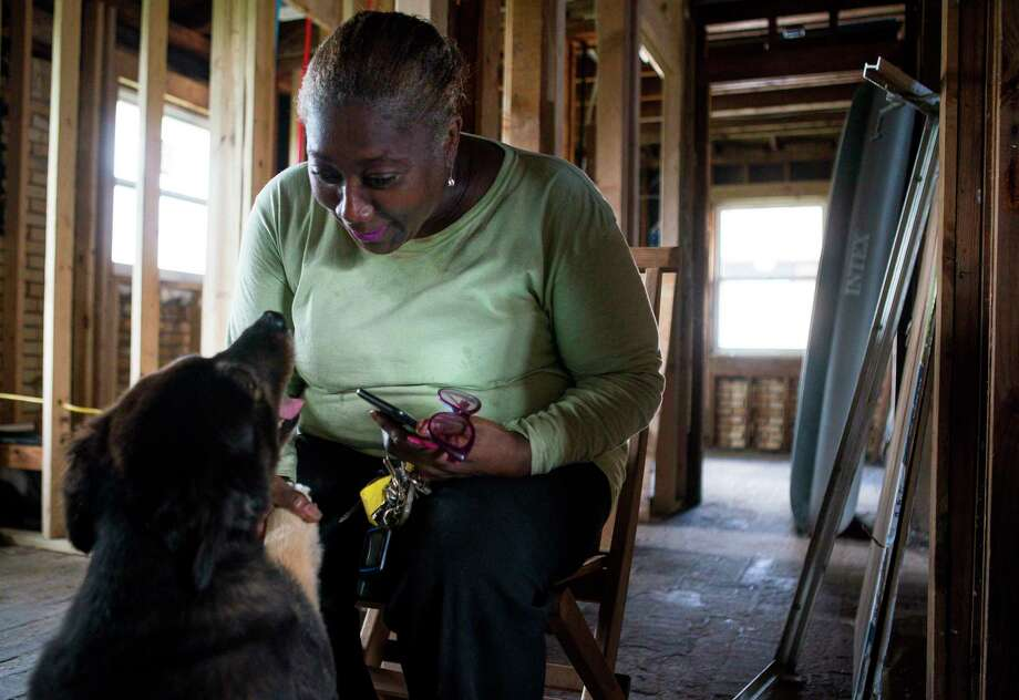 Alberta Fleming pets one of her dogs inside her northeast Houston home, Tuesday, May 28, 2019. Fleming's home was flooded during Hurricane Harvey, and now, almost two years later, it is only now starting to be repaired. Photo: Mark Mulligan,  Houston Chronicle / Staff Photographer / © 2019 Mark Mulligan / Houston Chronicle