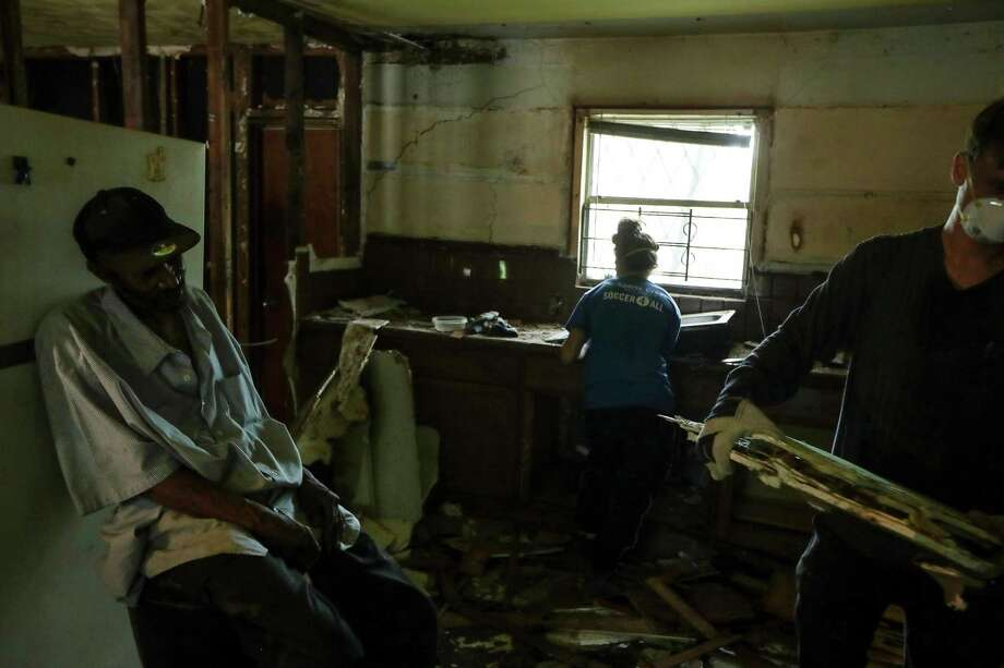 Ben Hirsch, right, and Becky Selle, center, work to demolish Malberth Moses' kitchen that was damaged during Hurricane Harvey, more than a year and a half after the storm, on Thursday, May 2, 2019, in Houston. Moses said he was suffering from cancer and took frequent breaks during the demolition. Photo: Jon Shapley,  Houston Chronicle / Staff Photographer / © 2019 Houston Chronicle