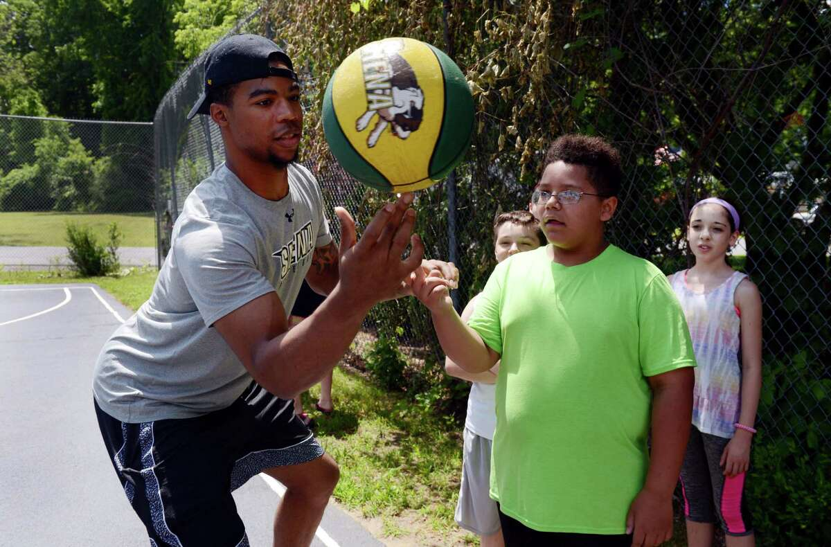 Elijah Burns of Troy, forward on Siena College Men's basketball team, left, tries to pass a spinning basketball to Jayden Ilert, 10, of Clifton Park, right, at CAPTAIN Community Human Services on Monday, July 1, 2019, in Clifton Park, N.Y. (Catherine Rafferty/Times Union)