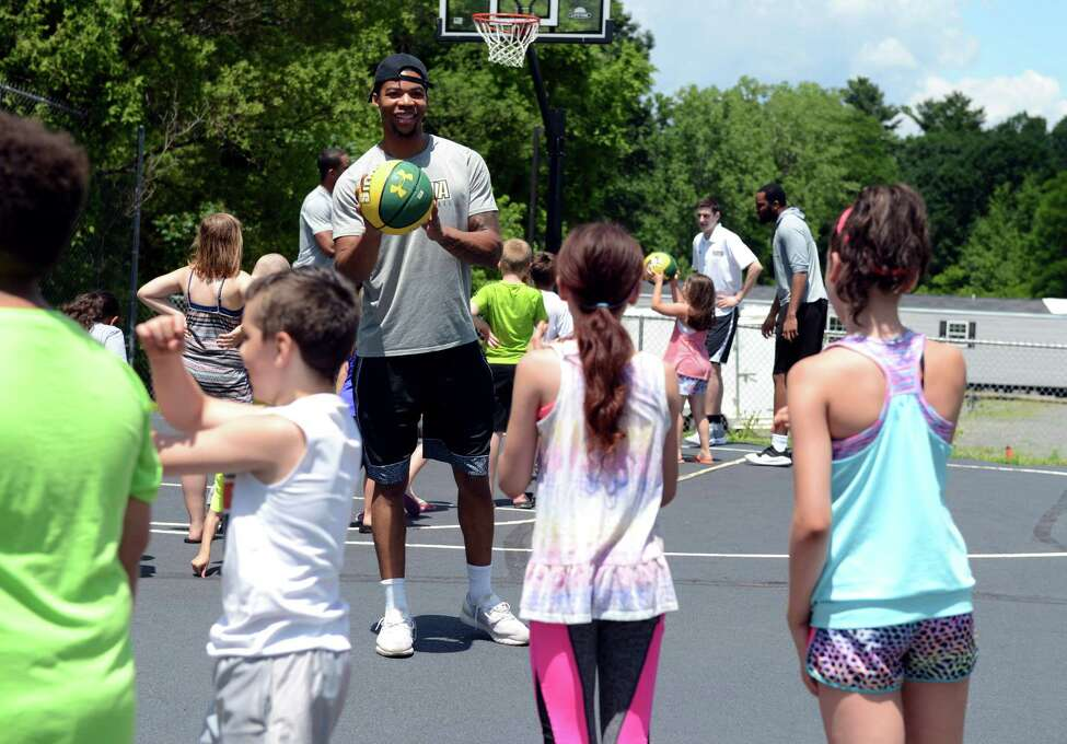 Elijah Burns of Troy, forward on Siena College Men's basketball team, center, does basketball drills with children at CAPTAIN Community Human Services on Monday, July 1, 2019, in Clifton Park, N.Y. CAPTAIN helps troubled teens, individuals and families in Saratoga County. (Catherine Rafferty/Times Union)