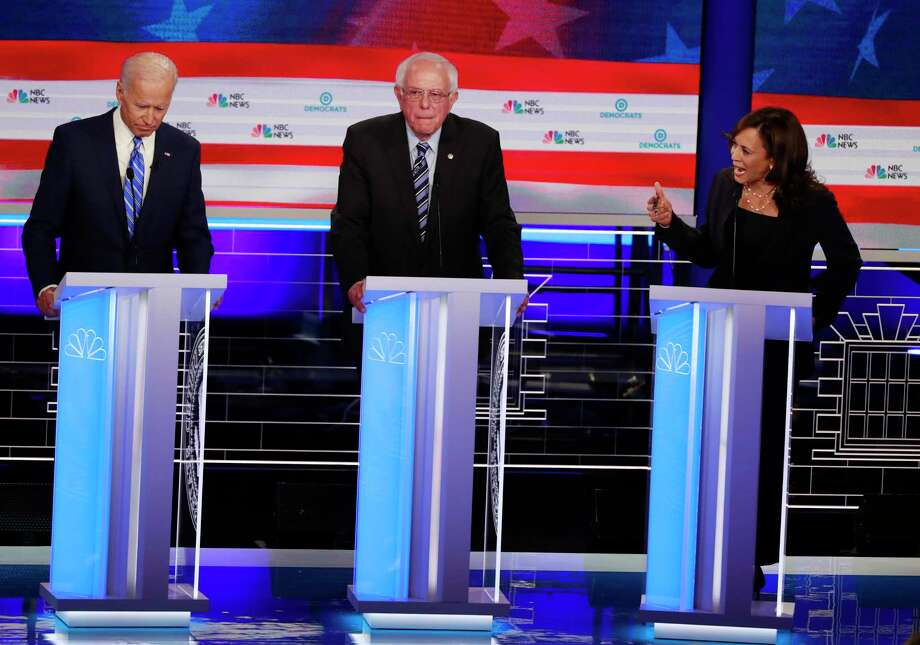 Democratic presidential candidate former Vice-President Joe Biden, left, and Sen. Kamala Harris, D-Calif., spar during the Democratic primary debate hosted by NBC News at the Adrienne Arsht Center for the Performing Arts, Thursday, June 27, 2019, in Miami. Sen. Bernie Sanders, I-Vt., is in the center. (AP Photo/Wilfredo Lee) Photo: Wilfredo Lee / Associated Press / Copyright 2019 The Associated Press. All rights reserved.