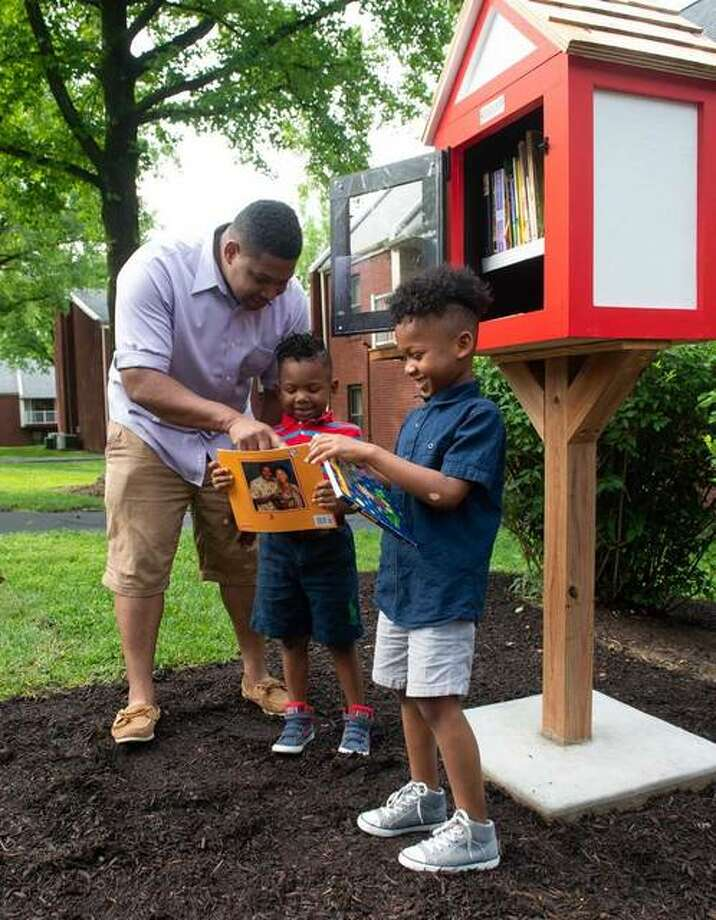 Cougar Village resident Tyrone Johnson and his sons, Charles and Tyrone, enjoy books from the new Little Free Library. Photo: For The Intelligencer