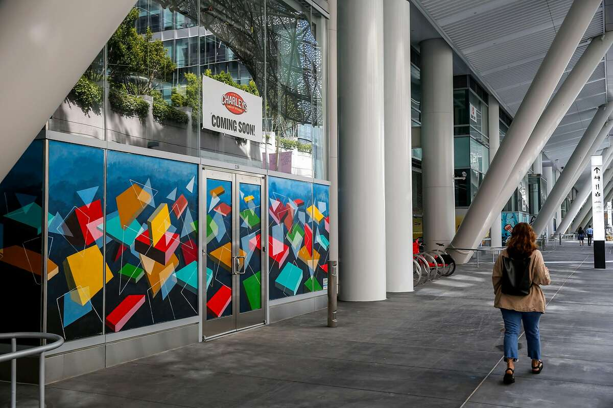 A woman walks past a future storefront of the reopened Salesforce Transit Center rooftop park Monday, July 1, 2019, in San Francisco, Calif. The transit center was initially opened in August 2018 but closed a month later after a cracked beam supporting the rooftop was discovered. After a nine month construction period to fix the issue the rooftop park has now reopened.