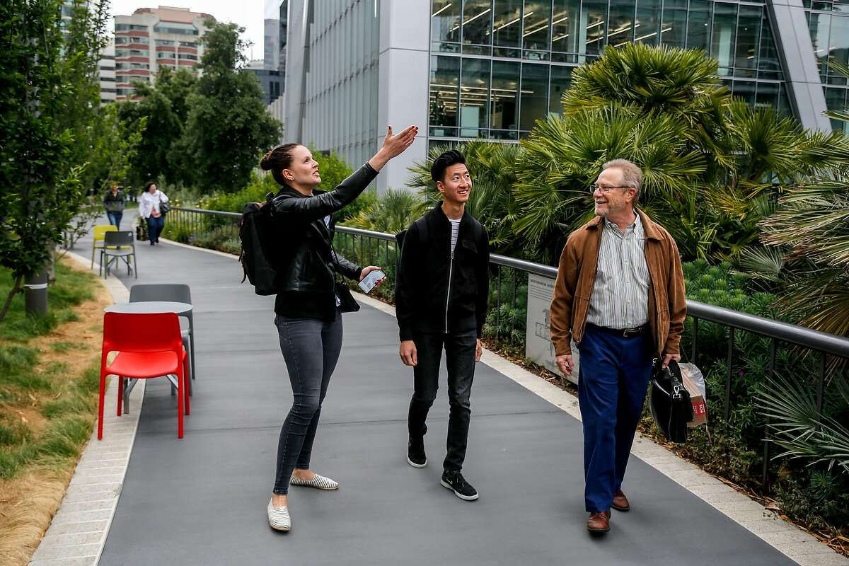 Renee Meppen of Amsterdam points out a building to Jeremiah Liem, also of Amsterdam, and Ed Caplan of Oakland as they explore the reopened Salesforce Transit Center rooftop park Monday, July 1, 2019, in San Francisco, Calif. The transit center was initially opened in August 2018 but closed a month later after a cracked beam supporting the rooftop was discovered. After a nine month construction period to fix the issue the rooftop park has now reopened.