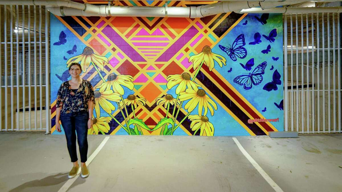 Houston artist Patricia Barrera poses with one of three murals she has created for the garage entrance of Drewery Place, Caydon USA's first highrise apartment building in Midtown.
