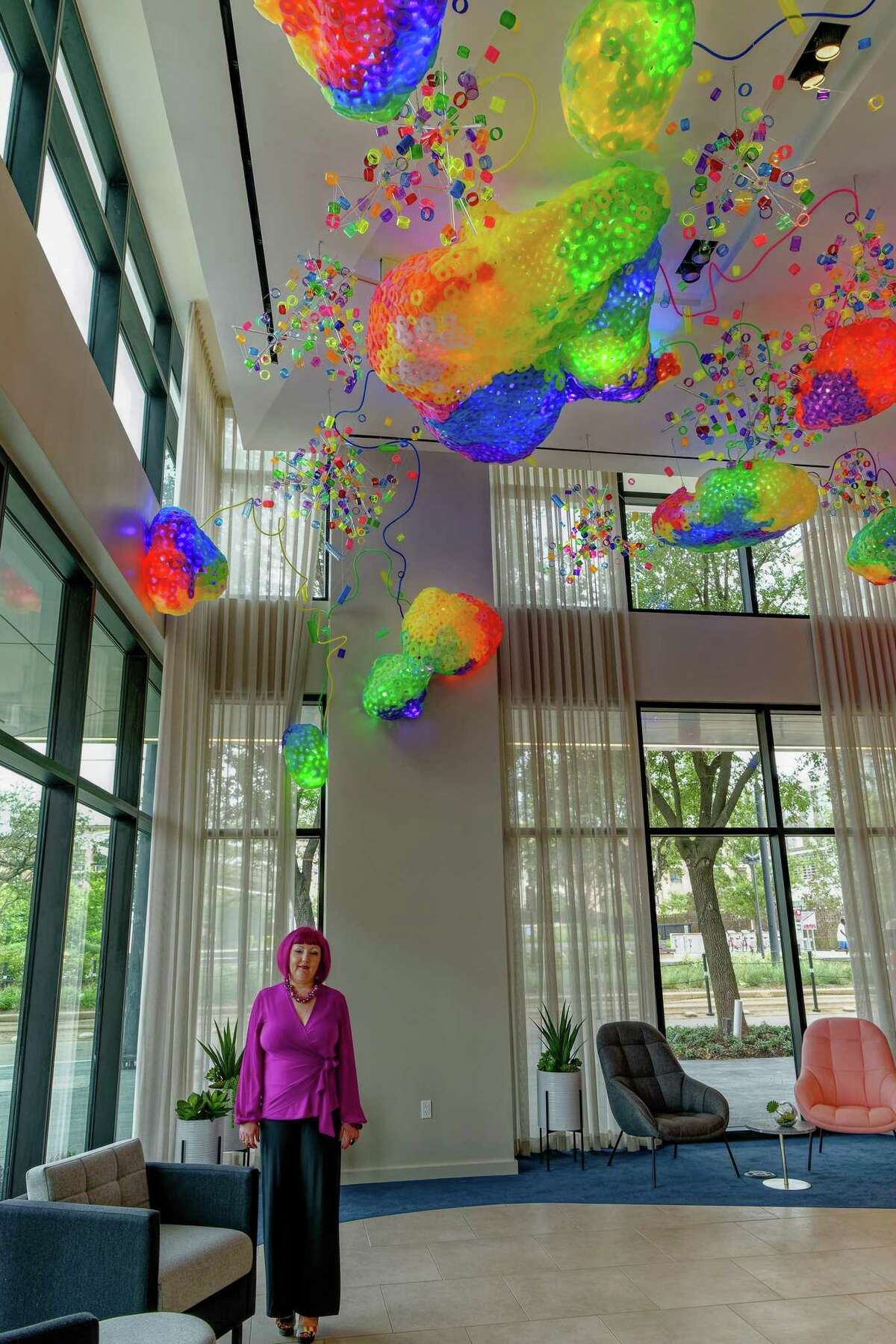 """Houston artist Adela Andea poses below """"The Great Barrier Reef,"""" her permanent installation for the lobby of Drewery Place, a new highrise project of the Australian firm Caydon USA in Midtown."""