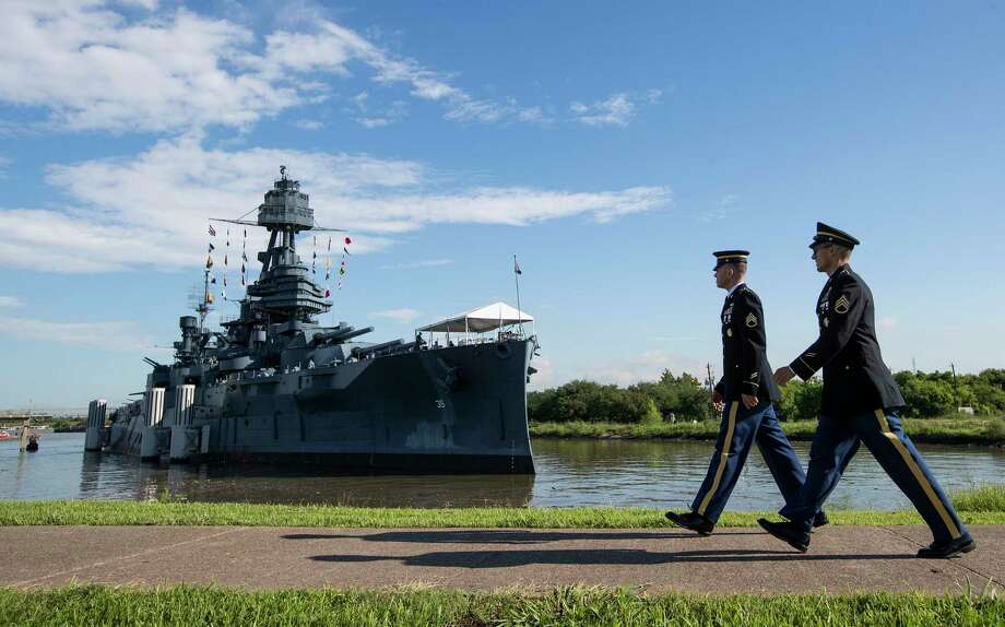 FILE - In this June 6, 2019 file photo, Army Staff Sgt. Jacob Klein, left, and Staff Sgt. Joel Ocasio walk past Battleship Texas to participate in a ceremony commemorating the 75th anniversary of D-Day, in La Porte, Texas. Public visits to the 107-year-old vessel near Houston will be limited during cataloging of thousands of artifacts on board amid plans for $35 million in ship repairs. The Texas Parks & Wildlife Department on Friday, June 28, 2019, announced , starting July 8, the vessel at the Battleship Texas State Historic Site in La Porte will close to visitors Monday through Thursday. The ship will be open Friday through Sunday. (Brett Coomer/Houston Chronicle via AP, File) Photo: Brett Coomer, MBO / Associated Press / Houston Chronicle