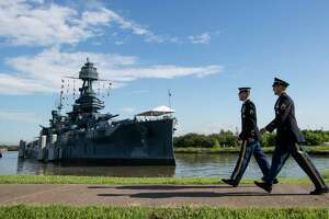 FILE - In this June 6, 2019 file photo, Army Staff Sgt. Jacob Klein, left, and Staff Sgt. Joel Ocasio walk past Battleship Texas to participate in a ceremony commemorating the 75th anniversary of D-Day, in La Porte, Texas. Public visits to the 107-year-old vessel near Houston will be limited during cataloging of thousands of artifacts on board amid plans for $35 million in ship repairs. The Texas Parks & Wildlife Department on Friday, June 28, 2019, announced , starting July 8, the vessel at the Battleship Texas State Historic Site in La Porte will close to visitors Monday through Thursday. The ship will be open Friday through Sunday. (Brett Coomer/Houston Chronicle via AP, File)