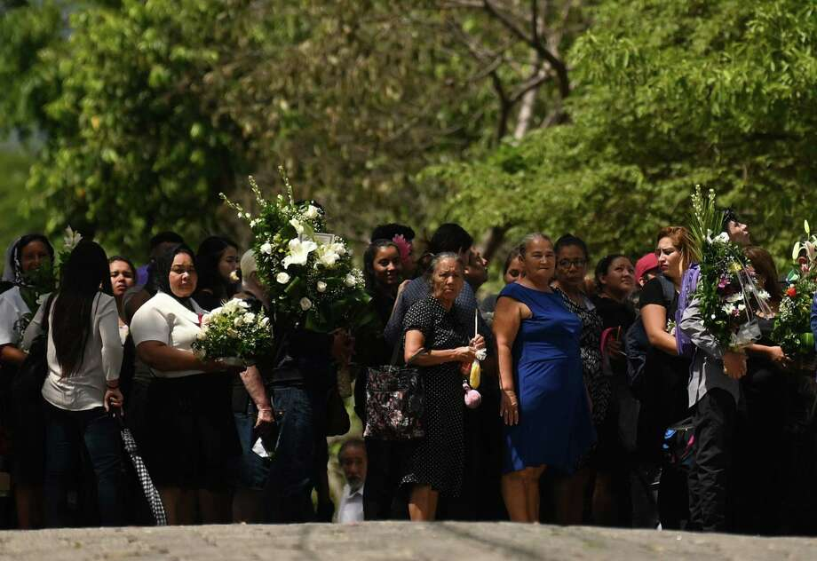 People attend the funeral of Salvadoran migrant Oscar Martinez and his almost two-year-old daughter Angie Valeria, who both drowned while trying to cross the Rio Grande from Mexico to the United States, at La Bermeja cemetery in San Salvador on July 1, 2019. - A shocking photo of the lifeless bodies of Martinez, who was 25, and his 23-month-old daughter Valeria lying face down in the border river fueled concern and outrage around the world, with some people blaming the US crackdown on border crossings for their deaths. (Photo by Marvin RECINOS / AFP)MARVIN RECINOS/AFP/Getty Images Photo: MARVIN RECINOS, Contributor / AFP/Getty Images / AFP or licensors