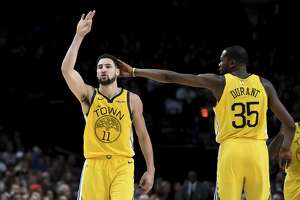 Golden State Warriors guard Klay Thompson, left, is patted on his head by forward Kevin Durant, right, after hitting a shot late in an NBA basketball game against the Portland Trail Blazers in Portland, Ore., Saturday, Dec. 29, 2018. The Warriors won 115-105. (AP Photo/Steve Dykes)