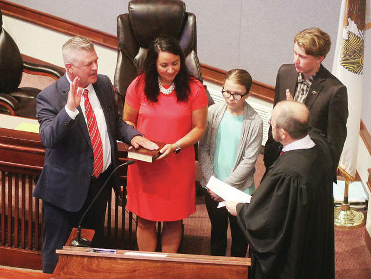 New Madison County Regional Superintendent of Schools Robert Werden, left, is sworn by Circuit Judge David Dugan Monday in the Madison County Board room. With Werden are his wife, Nancy, also an educator; daughter, Remington; and son, Bobby.