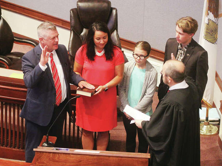 New Madison County Regional Superintendent of Schools Robert Werden, left, is sworn by Circuit Judge David Dugan Monday in the Madison County Board room. With Werden are his wife, Nancy, also an educator; daughter, Remington; and son, Bobby. Photo: Scott Cousins | The Intelligencer