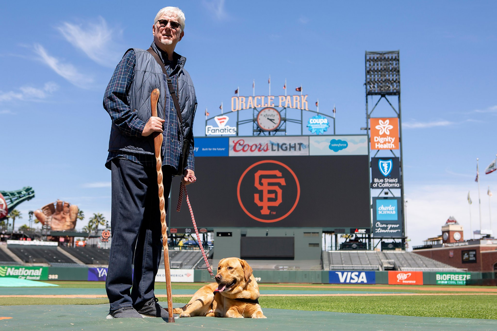 Giants announcer Mike Krukow leans on his service dog, Patriot, for support