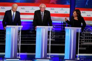 Democratic presidential candidate former Vice-President Joe Biden, left, and Sen. Kamala Harris, D-Calif., spar during the Democratic primary debate hosted by NBC News at the Adrienne Arsht Center for the Performing Arts, Thursday, June 27, 2019, in Miami. Sen. Bernie Sanders, I-Vt., is in the center. (AP Photo/Wilfredo Lee)