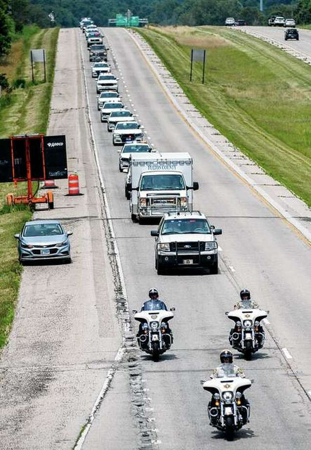 A long line of emergency vehicles, including an ambulance carrying the remains of Fulton County Deputy Troy Chisum, heads toward the Illinois Route 116 exit on Interstate 74 en route to a Lewistown funeral home Wednesday in Peoria. Chisum was shot to death June 25 while responding to a domestic disturbance call in rural Avon. Photo: Matt Dayoff | Journal Star Via AP