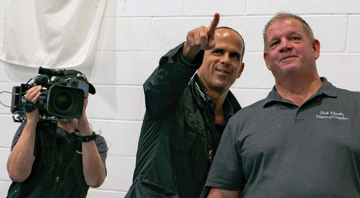 """CNBC """"The Profit"""" host Marcus Lemonis speaks to Grafton Mayor Rick Eberlin during a town hall meeting at Grafton Elementary School, where Lemonis announced his plans to help the city recover from this year's flooding."""
