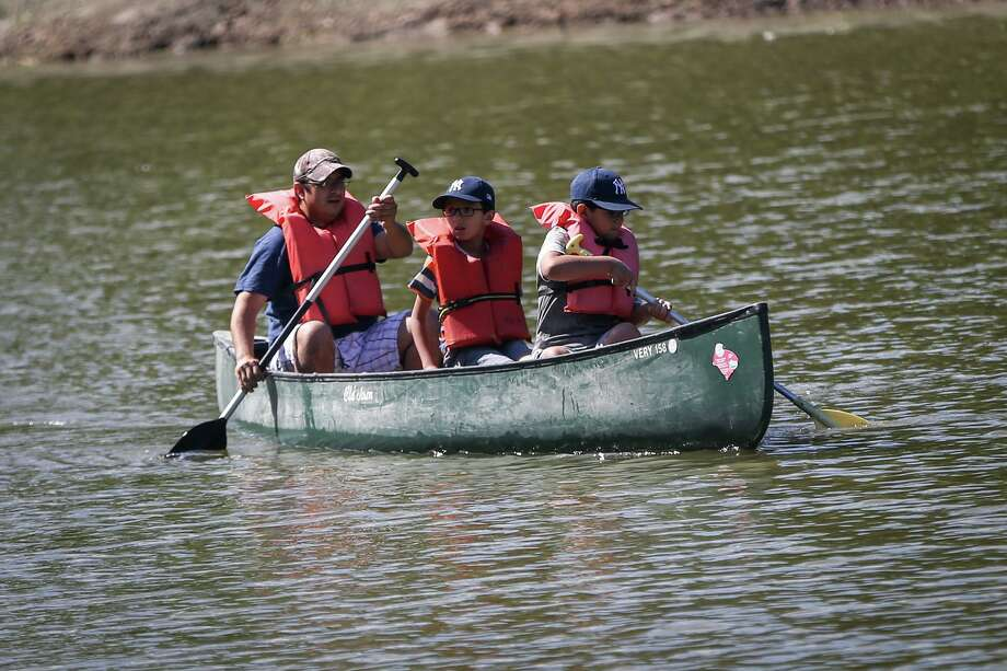 A family glides across the water in a canoe during the Kids on the Lake event at YMCA Camp Owen. Take time to get outside and away from behind a screen this summer. Photo: Michael Minasi, Staff Photographer / Houston Chronicle / © 2017 Houston Chronicle