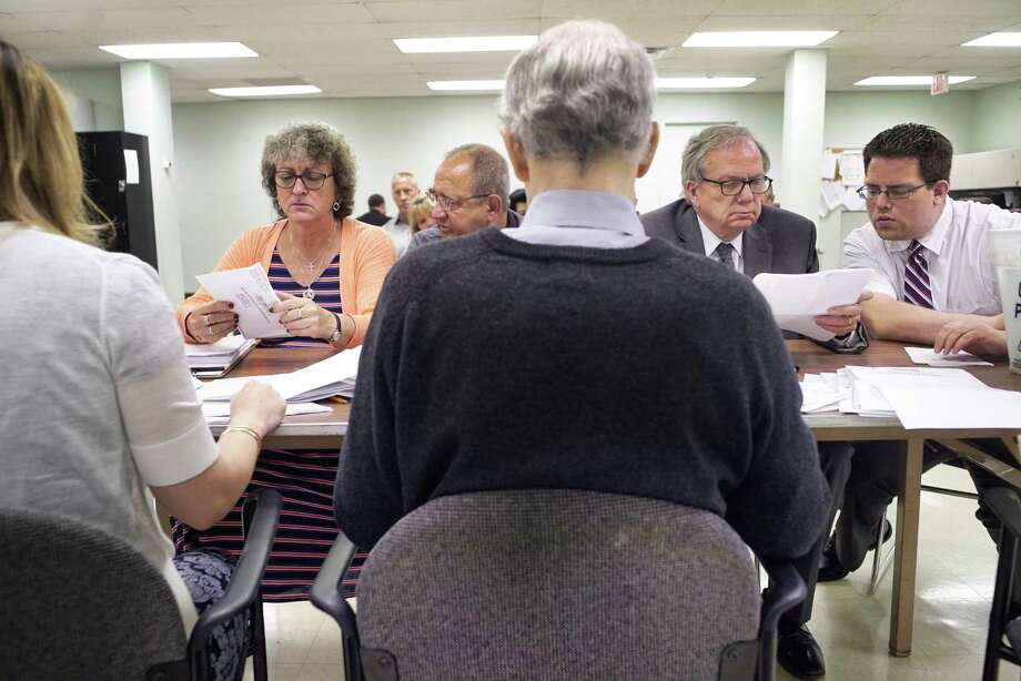 Candidates for Cohoes Common Council, 5th Ward, Kathy Donovan, left, and Adam Biggs, right, look over absentee ballots at the Albany County Board of Elections on Tuesday, July 2, 2019, in Albany, N.Y. Also pictured are, Gil Ethier, second from left, Chairman of the Cohoes Democratic Party and Deputy Majority Leader for the Albany County Legislature, and Tom Keefe, second from right. After the counting of absentee ballots, Donovan and Biggs are tied.  (Paul Buckowski/Times Union) Photo: Paul Buckowski, Albany Times Union / (Paul Buckowski/Times Union)