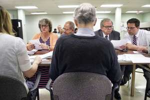 Candidates for Cohoes Common Council, 5th Ward, Kathy Donovan, left, and Adam Biggs, right, look over absentee ballots at the Albany County Board of Elections on Tuesday, July 2, 2019, in Albany, N.Y. Also pictured are, Gil Ethier, second from left, Chairman of the Cohoes Democratic Party and Deputy Majority Leader for the Albany County Legislature, and Tom Keefe, second from right. After the counting of absentee ballots, Donovan and Biggs are tied.  (Paul Buckowski/Times Union)