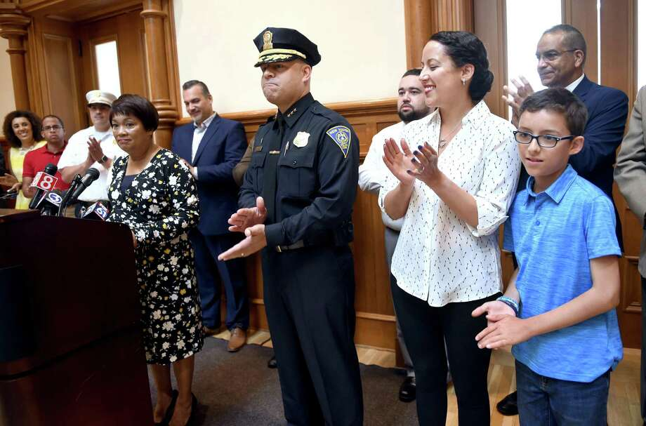 New Haven Interim Police Chief Otoniel Reyes, center, is applauded as New Haven Mayor Toni Harp, left, announced him as her selection to be the new police chief pending approval from the Board of Alders during a press conference at City Hall in New Haven July 2, 2019. At right is Reyes' wife, Leslie, and son, David, 10. Photo: Arnold Gold / Hearst Connecticut Media / New Haven Register