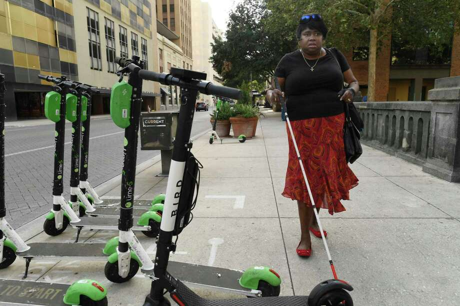 Athalie Malone, who is blind, encounters scooters on a sidewalk along Market Street on the way to a city government meeting. She chairs San Antonio's disability access advisory committee and says she has twice tripped over scooters downtown. Photo: Billy Calzada /Staff File Photo / San Antonio Express-News