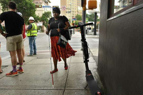 Athalie Malone, who is blind, walks by a scooter parked on a sidewalk along Navarro Street on her way to a city government meeting last month. Malone is on the selection committee that will determine which e-scooter companies will be awarded lucrative long-term city contracts, and her left arm is currently in a sling from her third downtown stumble this year over an abandoned scooter.