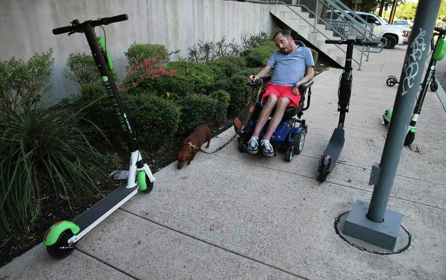 Adam Boffa, who relies on a wheelchair for mobility, and his pet Dachshund navigate past a collection of scooters in the Southtown area last month.. Boffa is exasperated with scooters and bicycles parked along sidewalks and ramps. The disabled community, especially people in wheelchairs and the blind, often feel their rights under the Americans with Disabilities Act have been ignored by scooter riders and companies, and the cities that permit their operations. (Kin Man Hui/San Antonio Express-News) Photo: Kin Man Hui /Staff Photographer / ©2019 San Antonio Express-News