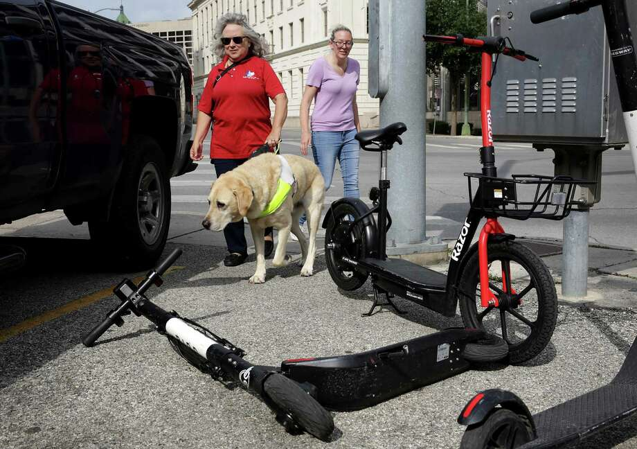 Jamie Massey, right, of Guide Dogs of Texas, assists Lou Ann Williams and her guide dog Atlas around scooters near Alamo Plaza last month. Photo: Bob Owen /Staff Photographer / ©2019 San Antonio Express-News