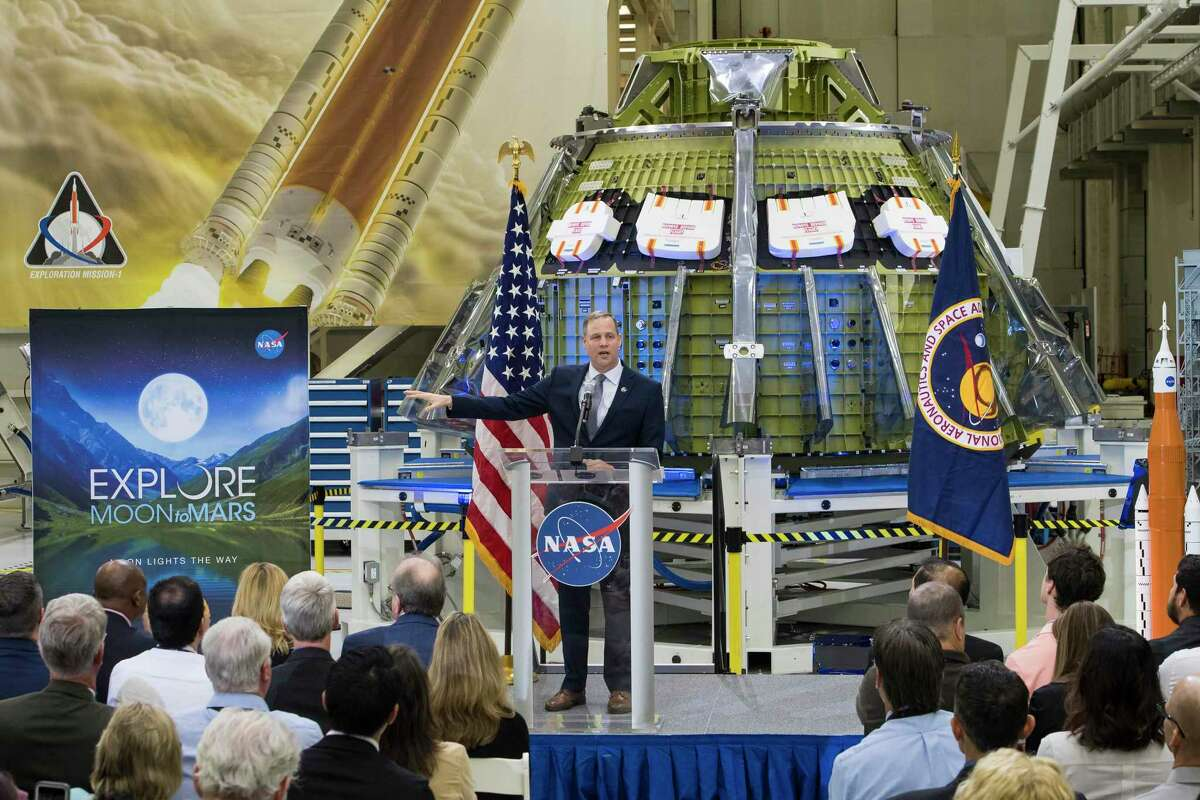 """A photo provided by NASA of Jim Bridenstine, NASA's administrator, speaking at the Kennedy Space Center in Cape Canaveral, Fla., surrounded by pictures and models of the Space Launch System, March 11, 2019. Mounting delays to the Space Launch System, primarily built by Boeing, are leading the agency to consider alternative forms of transport. """"NASA has a history of not meeting launch dates,"""" Bridenstine said, """"and I'm trying to change that."""""""