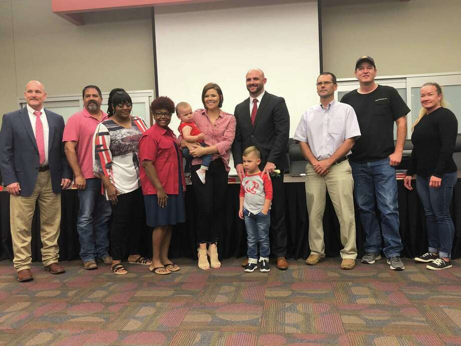 Dustin Bromley poses for a picture with his wife Erin, children Owen and Liam and the Crosby ISD Board of Trustees after being unanimously approved as Crosby High School principal Photo: Elliott Lapin / Staff Photo
