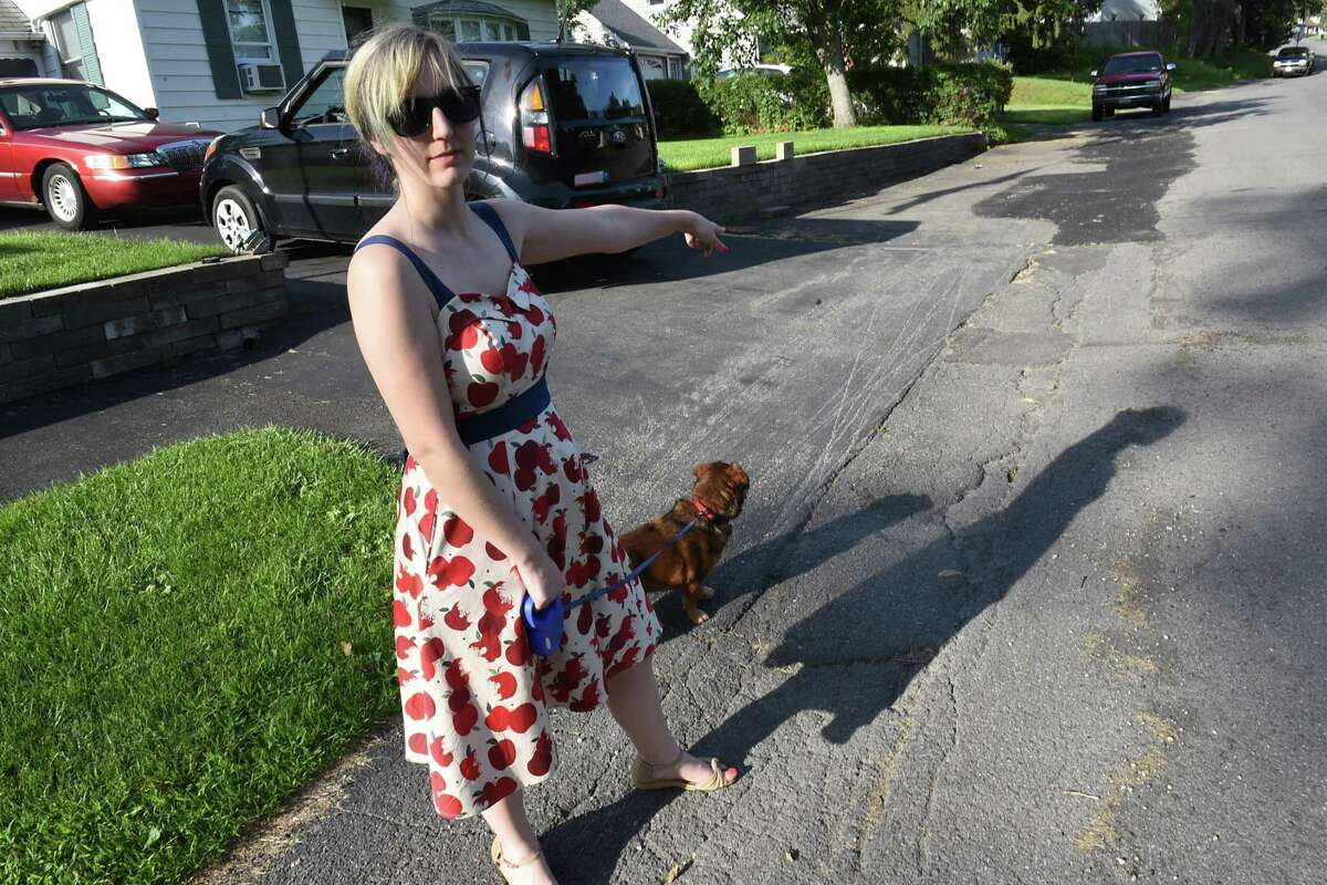 Caitlin Perry points to the patched up pavement on Glennon Rd. as she walks her dog Jonas on Monday, July 1, 2019 in Latham, N.Y. Caitlin Perry showed up at Colonie Town Board recently to petition the town to pave, not just patch, her road that hasn't been redone in 30 years. (Lori Van Buren/Times Union)