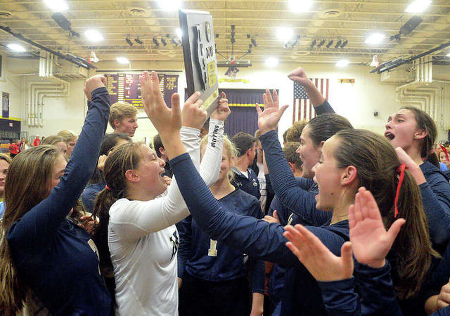 FMCHS libero Macy Hoppes holds the championship plaque as the Father McGivney High school girls volleyball team celebrates its win over Waterloo Gibault on Wednesday in the title match of the Class 1A Valmeyer Sectional. Photo: Scott Marion|The Intelligencer