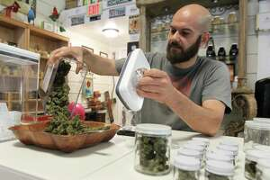 Samuel Luques-Martin, owner of Happy Hippy Haus, pours hemp flowers into a container to sort at his business on Texas-105, Tuesday, July 2, 2019, in Cleveland.