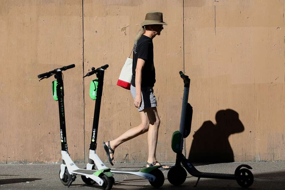 FILE - A pedestrian walks past Lime scooters in front of the Uptown Station, located at 1955 Broadway, in Oakland, Calif. on Tuesday, October 16, 2018. Hundreds of Lime bikes and scooters were burned in a fire at a Spokane Valley warehouse. Photo: Yalonda M James / The Chronicle 2018
