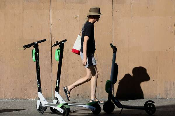 A pedestrian walks past Lime scooters in front of the Uptown Station, located at 1955 Broadway, in Oakland, Calif. on Tuesday, October 16, 2018. Sources say Juul and Microsoft/LinkedIn are considering leases there.