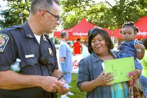 Hamden Police Capt. Ronald Smith, left, chats with Shanelle Robinson, who is holding her two-year-old daughter, Serenity, at a past  National Night Out in Hamden
