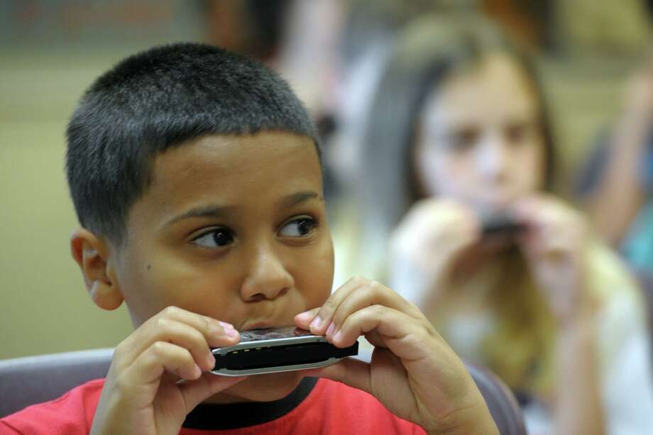 Joseph Iannaccone, of Seymour, plays his first notes on his new harmonica during a workshop at the Edith Wheeler Memorial Library, in Monroe, Conn. July 2, 2019. Photo: Hearst Connecticut Media / Connecticut Post