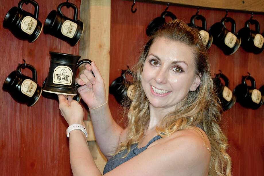 A customer chooses her own mug at the Little Red Barn Brewery in Winsted. Photo: Lara Green-Kazlauskas  / For Hearst Connecticut Media /