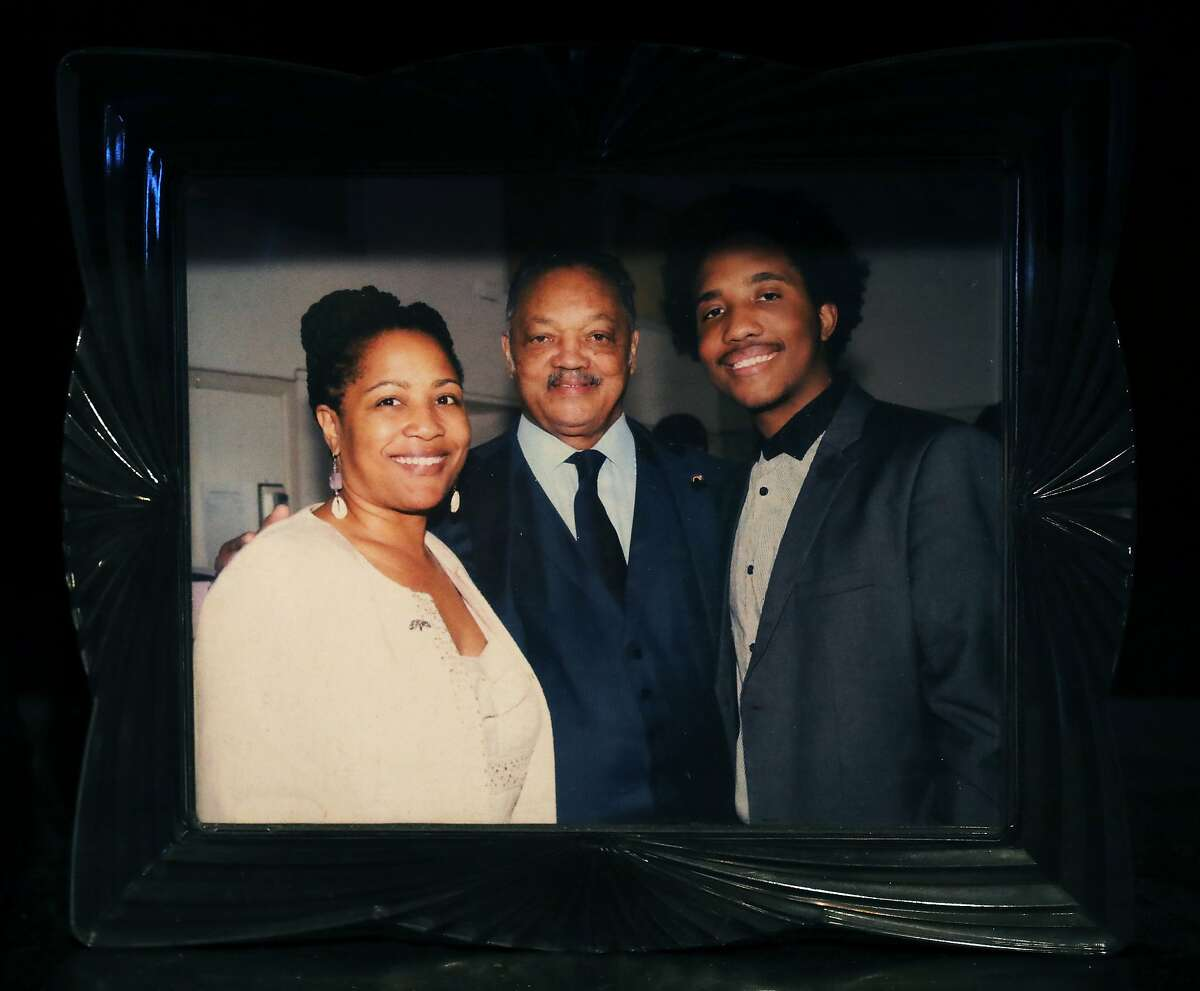 An undated image shows Oakland councilwoman Lynette McElhaney posing for a portrait with Rev. Jesse Jackson and her son, Victor, as she holds a prayer service in her Oakland home to honor her slain son in Oakland, Calif., on Friday, April 5, 2019. Victor McElhaney, 21, was fatally shot last month during an armed robbery attempt in Los Angeles.