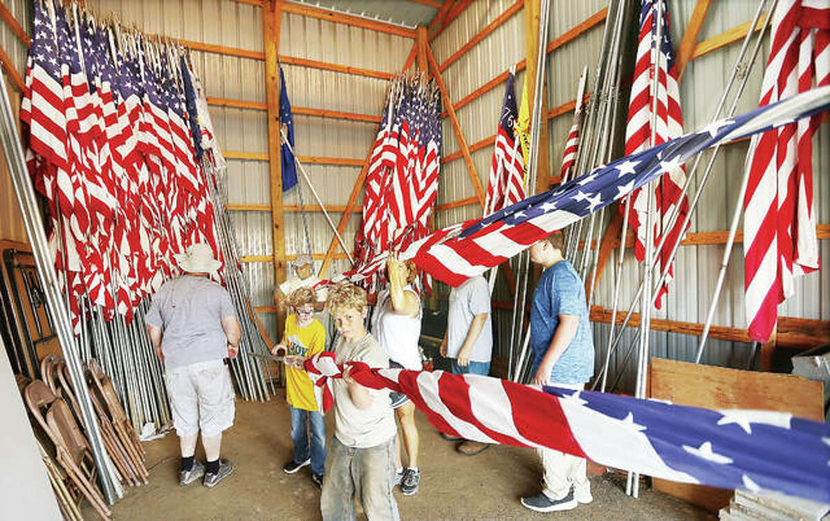 Members of Alton Boy Scout Troop 1 and Cub Scout Pack 1, who met at Alton VFW Post 1308, helped load the 40 large American flags the post was loaning for the Brighton display of the Moving Vietnam Memorial Wall early Tuesday morning. The three-fifths scale replica of the Washington monument stopped at the Alton post Tuesday for an escort to Schneider Park in Brighton where it will be open to the public at 6 p.m. today through 9 p.m. Saturday night. Volunteers are being sought Sunday morning to help disassemble the wall.