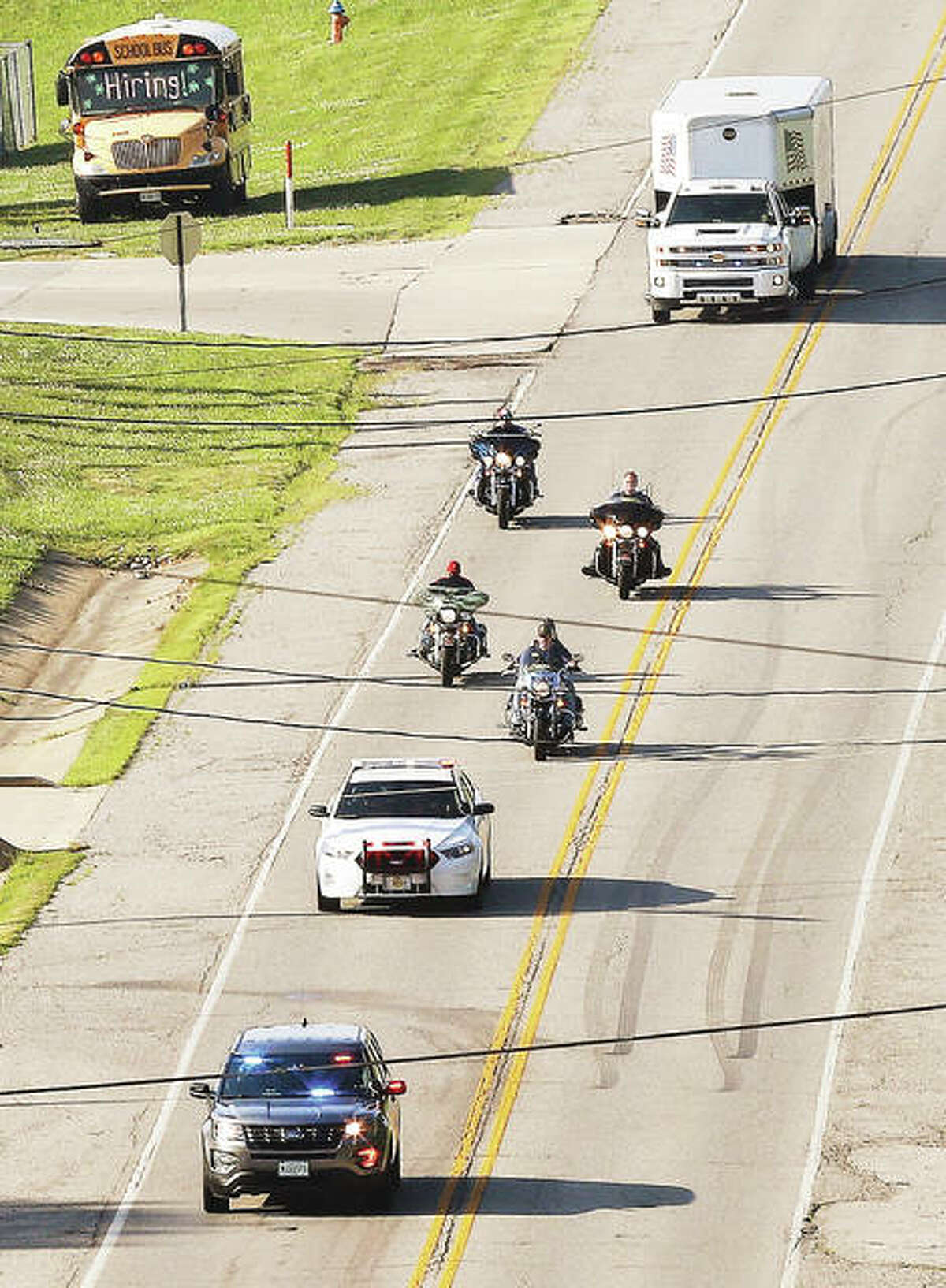 A procession up North Alby Street - led by police, Patriot Guard motorcyclists and about 30 vehicles in all - escorts the Vietnam Traveling Memorial Wall to Brighton on Tuesday where 65 volunteers assembled it.