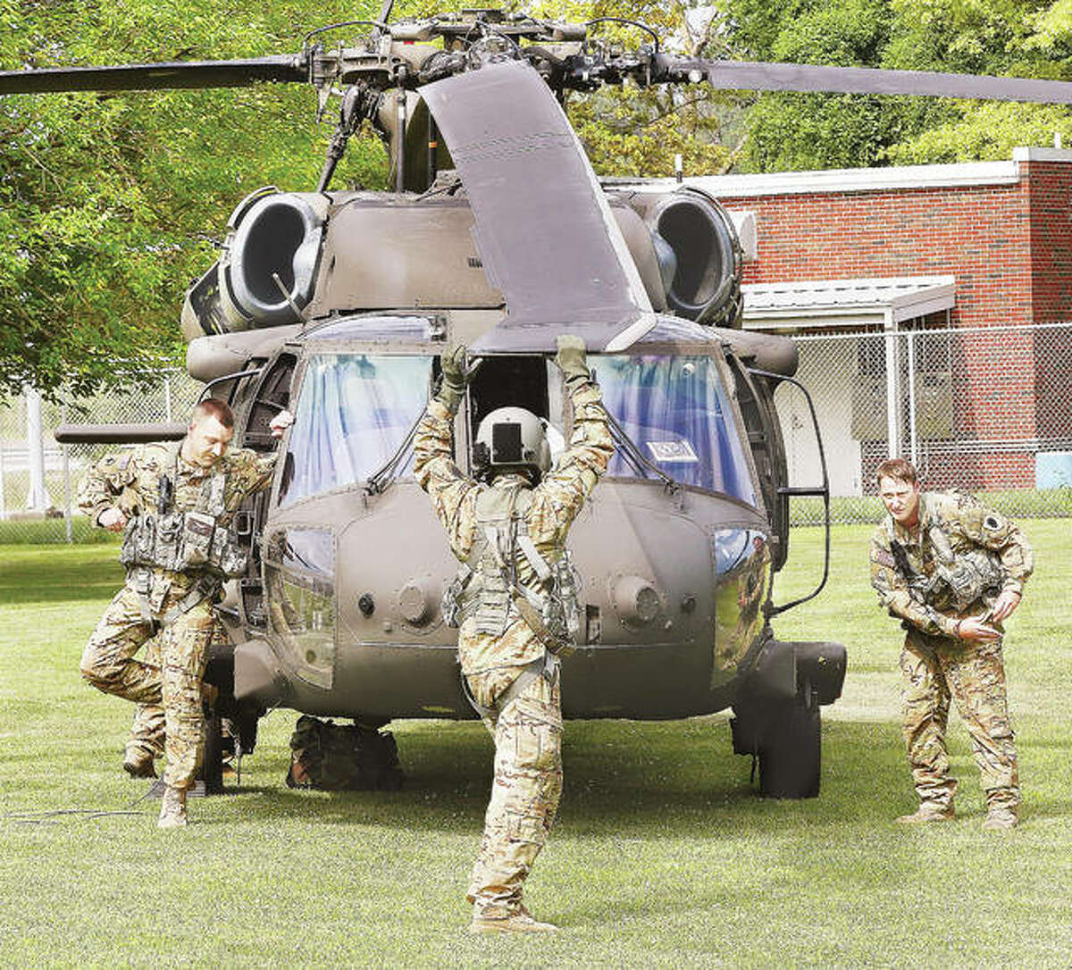 A National Guard member grabs a slowly spinning prop and stops it after the helicopter landed on the lawn behind the school.