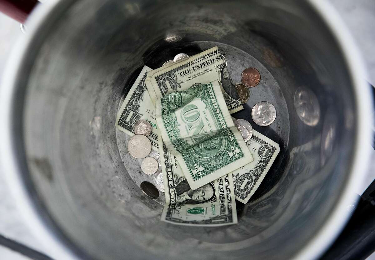 Money sits inside a metal tin given to Anthony Cordell as he plays the bass while panhandling inside the Civic Center BART Station in San Francisco, Calif. Tuesday, July 2, 2019.