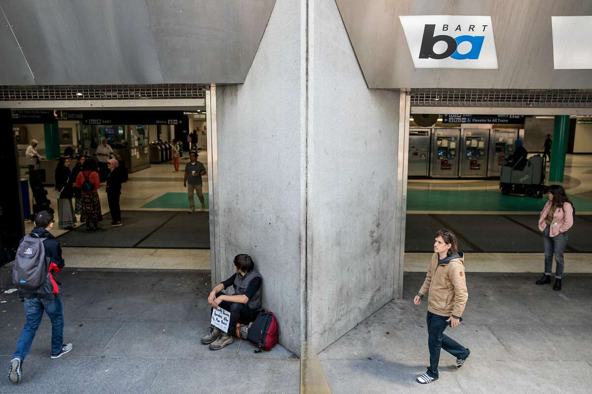 Jeffrey, who didn't provide his last name, panhandles while sitting outside of the Powell Street BART Station in San Francisco, Calif. Tuesday, July 2, 2019.