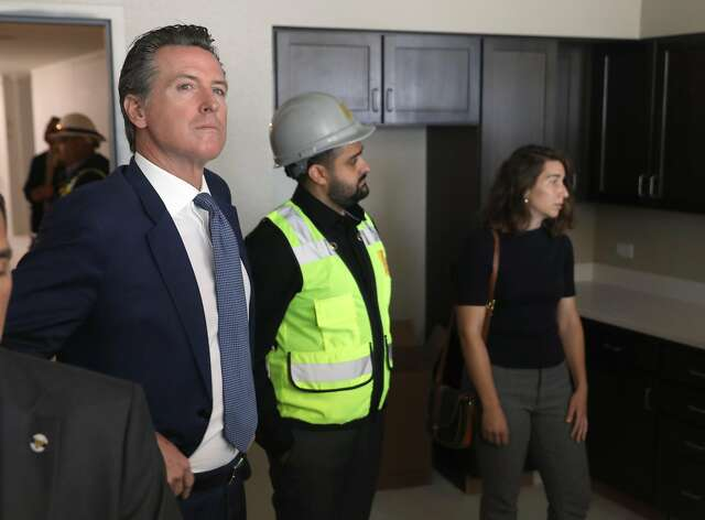 Newsom (left), JHF project manager Kyan Hakimi and Emeryville Mayor Ally Medina check out a kitchen at Estrella Vista Apartments.